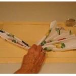 Segurando uma das extremidades das pregas, segure a peça no meio e dobre as pregas ao meio. Deslize um anel de guardanapo sobre a base das pregas.