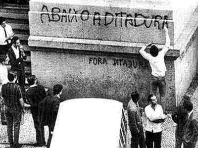 Jovem pichando frases de efeito contra a ditadura durante a Passeata dos 100 mil ocorrida em 26 de junho de 1968. Devido a repercussão dessa passeata, os militares instauraram o AI-5.