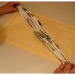 Segurando o guardanapo nas extremidades, pressione os vincos das dobras para que eles fixem no tecido.