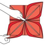 Com um dedo pressionando o centro do guardanapo, coloque a mão por baixo e puxe para cima a aba em cada canto para criar as pétalas de lótus.
