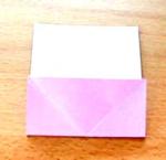 """Pelo centro do """"X"""" dobre o papel para trás."""